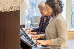 Music therapist playing piano with a patient.