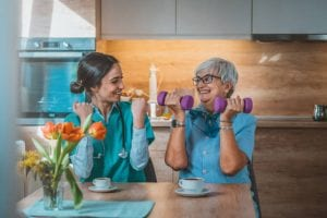 Photo of Nurse helping senior woman in lifting dumbbell at retirement home during the day. Senior woman with dumbbells in rehab with a physiotherapist smiling. Physiotherapist helps elderly woman with healthy dumbbell training in rehab or home in the kitchen while sitting at table.