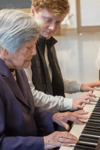 music therapy session, two people playing a piano